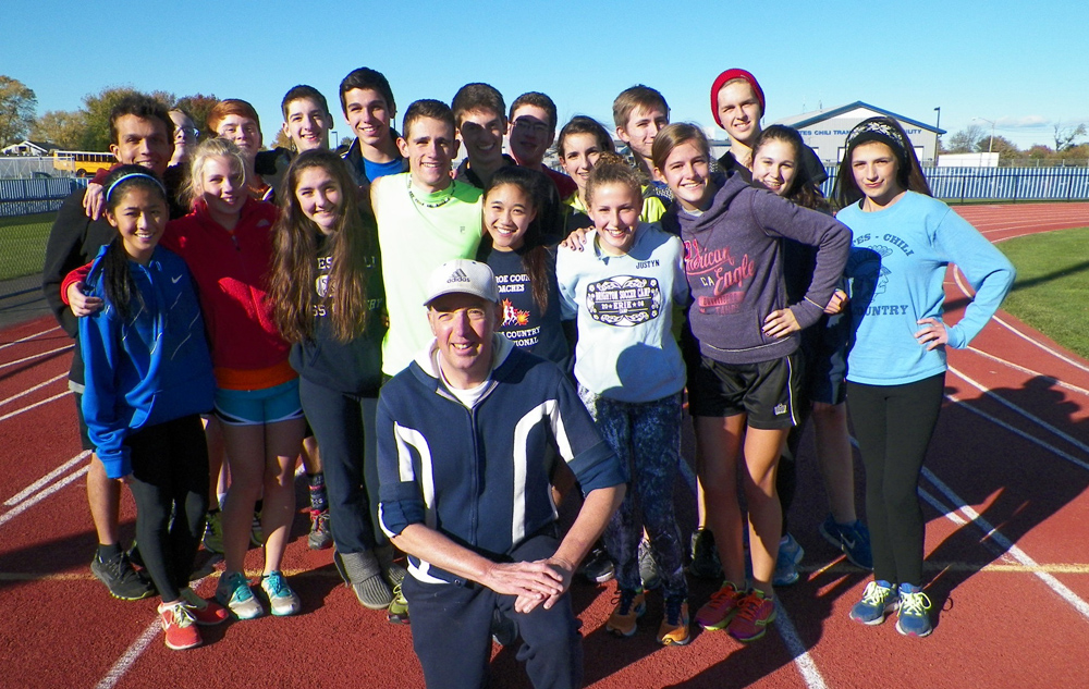 Gates senior runner Bruce Rychwalski poses with the Gates Chili High School boys and girls cross country team. Rychwalski, 64, a 2013 inductee into the Gates Chili Central School District Hall of Fame, went for a run with members of the boys cross country team on Monday, October 28. He completed 40 road races this year.