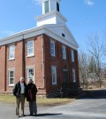Mary Edwards and Don Lage in front of the historic Clarkson Academy.