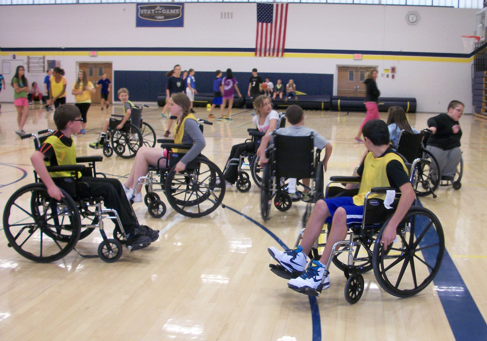 Students at Cosgrove Middle School in Spencerport try their skills at playing wheelchair basketball using rental chairs. The goal of the mini-unit was to help students get the experience of being in a wheelchair as their classmate, Jack Zyra, is. As