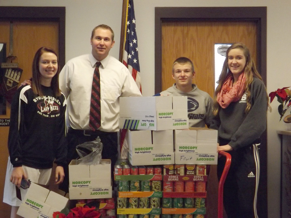 Varsity Club members and advisor Nick Muhlenkamp with the 2013 collected non-perishable food donations from the Swimming, Indoor Track, Girls' Basketball, and Boys' Basketball Teams.