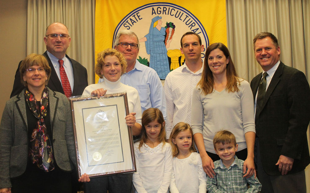 "Family farm receives Century Award: The New York State Agricultural Society honors families dedicated to farming, stewardship, and community involvement in New York. Robb Farms of Spencerport received recognition as a ""Century Farm"" for being in continuous family ownership and operation for over 100 years.  Robb Farms was established on April 1, 1912 by George Robb, Sr., whose parents were German immigrants. Current operators, Randall and Margery Robb, have owned Robb Farms since 1981. Initially the farm was planted to apples, sweet and sour cherries and peaches, raised beef cattle, mostly Angus, and grew potatoes. Today, more than 500 acres comprise the business.  Continuing the tradition of innovation and meeting market interest, they added Saskatoon Berries to their offerings in 2013, the only site in the county with availability. Shown at the Century Farm award presenation (l-r) front row: Diane Held, President, NYS Agricultural Society; Margie Robb, Audrey Nichols, Olivia Nichols, Drew Nichols; back row: Bill Lipinski, CEO, Farm Credit East (award sponsor); Randy Robb, Chris Nichols, Tracy Robb, Pat Hooker, Director of Agribusiness Development at Empire State Development. Photograph provided by the New York State Agricultural Society."