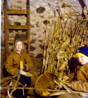 Grandchildren Emily and Lukas try their hand at husking corn the same way we used to do it, said Joe Reinschmidt.
