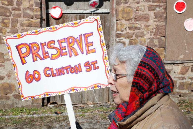 Helen Smagorinsky, noted local artist, holds a message sign.