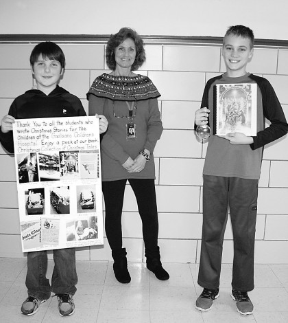 Ethan Hryhorenko (left) and Brandon Farrell, both sixth graders at Village Elementary School, along with Kathleen Neefe, a teacher's aide, with the book they helped write and a thank-you poster from Golisano Children's Hospital.