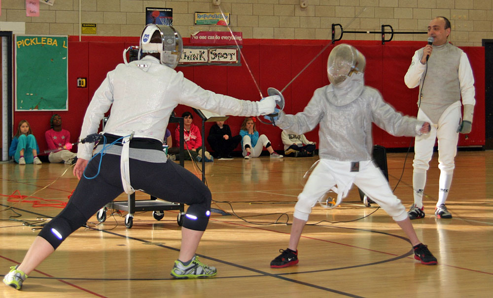 Christine Griffith, a Sabre coach at Rochester Fencing Club, and Alex Pickering, a student at Quest Elementary School in Hilton, demonstrate fencing for his fellow students. Semion Kiriakidi, a Foil and Sabre coach, referees the match.