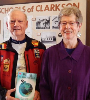 World cyclist Michael Fahey stands with Mary Edwards, president of the Clarkson Historical Society, prior to his presentation at the Clarkson Academy on April 2. He holds his recent publication Bicycling to Save My Soul: America, Ireland and England.