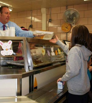 NYS Senator Joe Robach serves lunch to students at Village Elementary School in Hilton. He later addressed the students about the importance of eating healthy meals and sat down to enjoy lunch with a group of students.