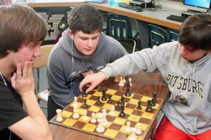 Eighth-graders Max Leisenring (left) and Joshua Fry (right) compete in the early rounds of the chess tournament as Tyler Lincoln observes.