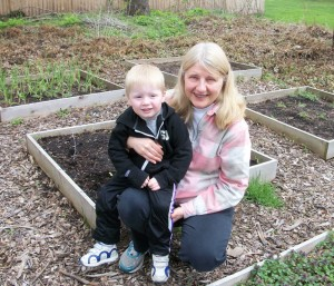 Jane Jones and her three-year-old grandson, Jaxon, in the garden area that surrounds the Coleman Avenue, Spencerport home. Jaxon loves to help his grandmother, especially with watering. Jane says the boxes are great because they are convenient and you can grow in areas with poor soil by filling the boxes with compost and organic material.