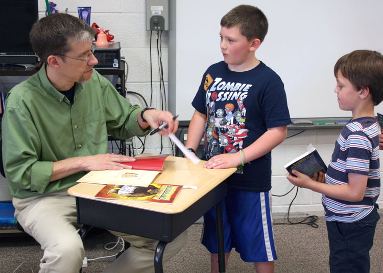 Visiting author Matthew McElligott gets up close and personal with first-grader Ruger Starowitz, one of his fans at Byron-Bergen Elementary School.
