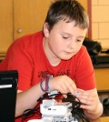 Ben Hassett, a fourth grader at Village Elementary School in Hilton, adjusts his Lego® robot.