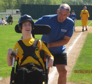 Volunteer Joe Setek helps Josh Lapp around the bases.
