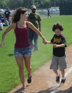 "Westside Challenger Baseball volunteer ""buddy"" Lysa Hoyt and Leo Mossa look to score a run."