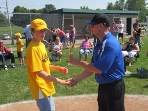Kirk Warren gets a congratulations and trophy from Coach Darren Zyra.