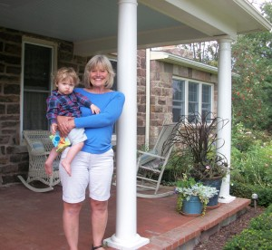 Denise Bedard on her porch holding 15-month old grandson, Beckett who already enjoys the garden.