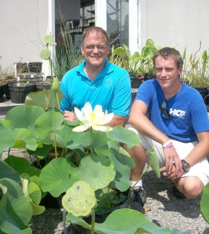 Larry Nau of Bergen Water Gardens & Nursery and his son, Nathan, pose with blooming lotus plants outside the nursery in Churchville. Nathan is a college student and helps out when he can. K. Gabalski photo.