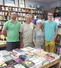 In transition - (l to r) John Bonczyk, Archie Kutz, Pat Kutz, and Cody Steffen stand in the Lift Bridge Book Shop on Main Street in Brockport. In January 2015, ownership will transfer from Archie and Pat to John and Cody.