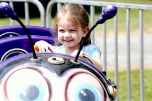 McKinley Curran, Fairport, 3, looks very happy to be driving her car in the Bees ride at the Hilton Fire Department Carnival. McKinley's grandmother is Laurie Curran of Hilton. Photograph by Walter Horylev.