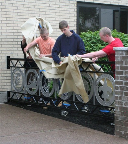 Students from the Engineering and Metal Fabrication program unveil one of the two railings outside of WEMOCO that they designed and manufactured.