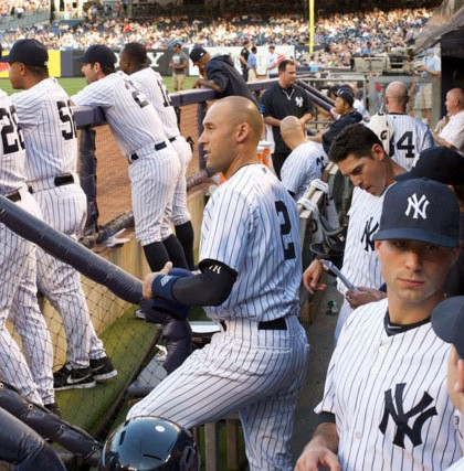 In the dugout during a game. Jeter is standing directly in front of Aaron.