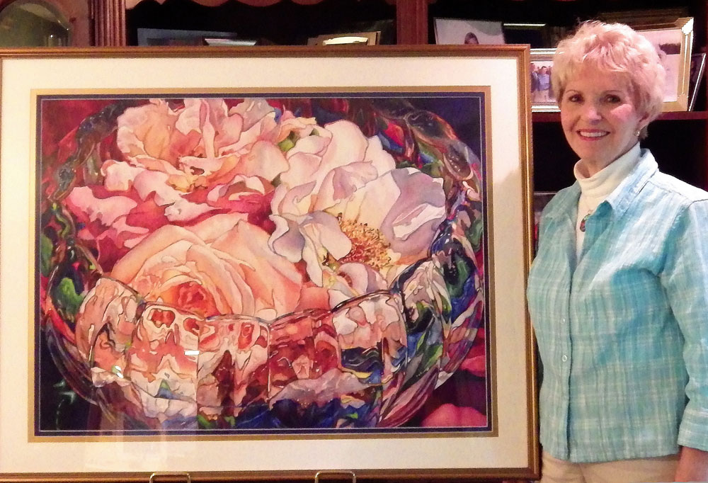 "Artist Dianne Hickerson stands with her painting ""Rose Bowl Three,"" one of her three watercolor paintings in the recently-published book The Artistic Touch 6."