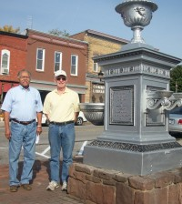 Holley Mayor John Kenney (left) and artist Tony Barry (right) standing next to the fountain in the center of Holley village.