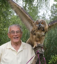 Walt and Goliath, two birds of a feather. Walter says the long wings stretch to an amazing width and once the owl stabilized on his arm he remained perched there, very still. Paul Schnell photo.