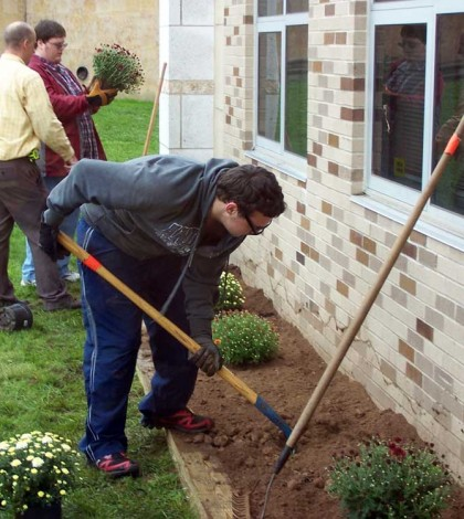 Hilton High School students Draven Rogers (front) and Andy Hall, along with their teacher Steve Randall, work on a garden they built on the school grounds. The class is growing its own plants and creating decorations for the space as part of a community service project.
