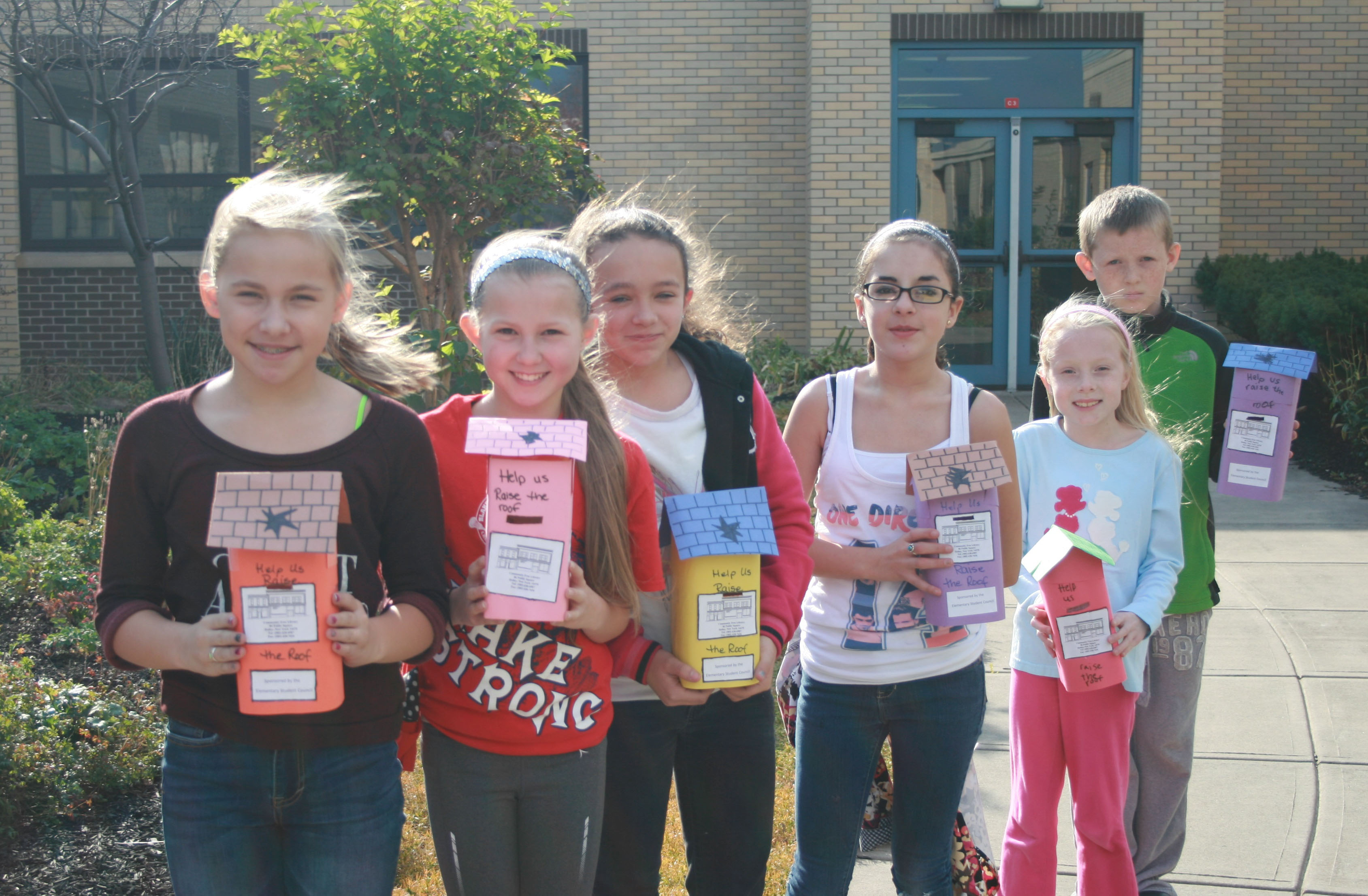 From left, Rachael Howard, Allyson Skehan, Makayla Famoly, Skyla Milazzo, Elise Quincey and Storm Boyce take their containers to Holley village businesses to help collect donations for the library fund.