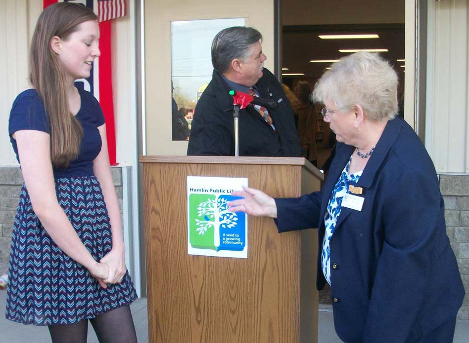 "Hilton Central School 11th grader Samantha Derousie and Hamlin Library Director Kay Hughes-Dennett pose with the new library logo designed by Derousie. The design also features the library's new slogan: ""A seed to a growing community."" K. Gabalski photo."