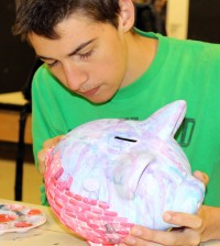 Hilton senior Matthew Palmeri paints a piggy bank for the Hilton Education Foundation. The banks are placed throughout the community to raise funds for the Cadet Cupboard, which provides food during school breaks for students in need.