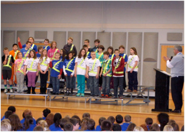 Brockport fourth- and fifth-grade students, led by Principal Sean Bruno, take the pledge to become Hill School Safety Patrol members.