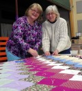 Judy Pray (left) and Penny Norton put the finishing touches on a quilt created by the Stitching Servants organization which they started at Brockport Free Methodist Church 15 years ago. Photo by Dianne Hickerson.