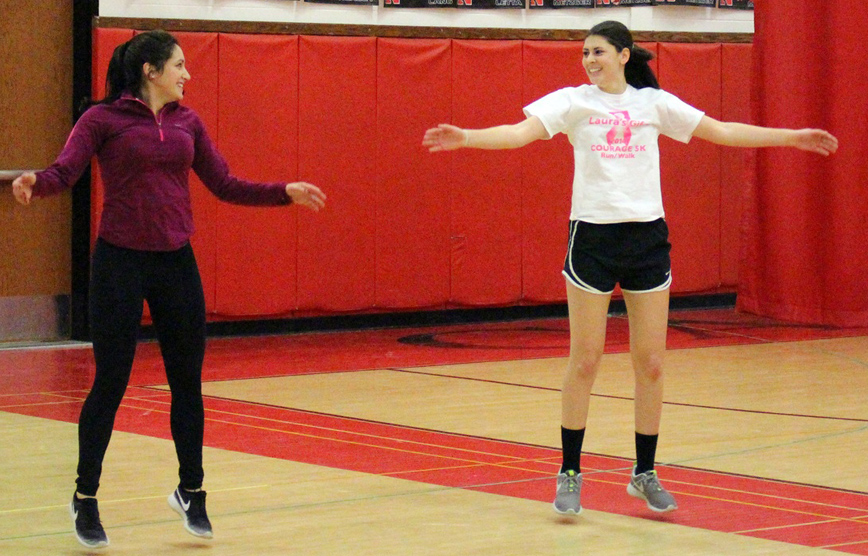 Hilton seniors Sophia Rivituso (left) and Gabrielle Prince have fun with the jumping jack portion of the Burp It On challenge in which their class is challenging students in Hilton and around the world to do 60 minutes of physical activity every day. The challenge is part of their IB Sports, Exercise and Health Science class.
