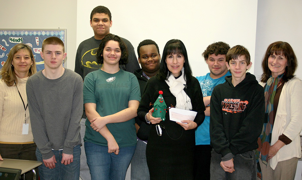 Class members present the Leukemia & Lymphoma Society's Gail Floros with a check for $897.80 and one of their handcrafted Christmas trees.