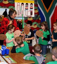 Education coordinator Claudia Newton, from Explore and More Children's Museum, uses masks to introduce Byron-Bergen first graders to the ethnic diversity of South Africa.