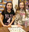 Hilton's Quest Elementary School students Julia Sciortino (left) and Ashley Simons serve up Peruvian cookies as part of their first Culture Day. They are students in David Budgar's intermediate class.