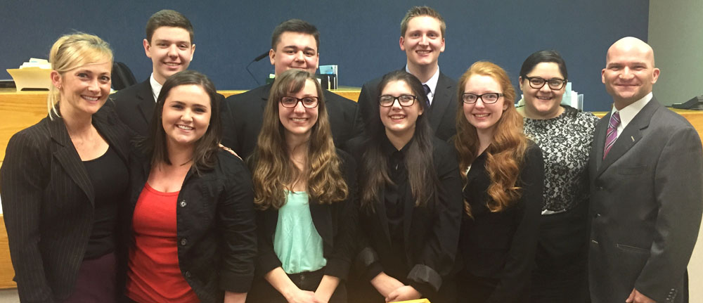 2015 Hilton High School Mock Trial Team and Monroe County Champions depicted in the submitted photograph are from left to right (front): Mary Pignato (Business Law Instructor and Team Coach); Kate West; Nicole Bradbury; Shannon McPhee; Alyssa Reese. Depicted left to right (back): Peter Shannon, Sam D'Angelo, Josh Mooney; Bianca S. D'Angelo, Esq. (Monroe County Assistant District Attorney and Team Coach); Hon. Michael A. Sciortino (Parma Town Justice and Team Coach).  (Photo Credit: Brian Bartalo, Principal of Hilton High School).