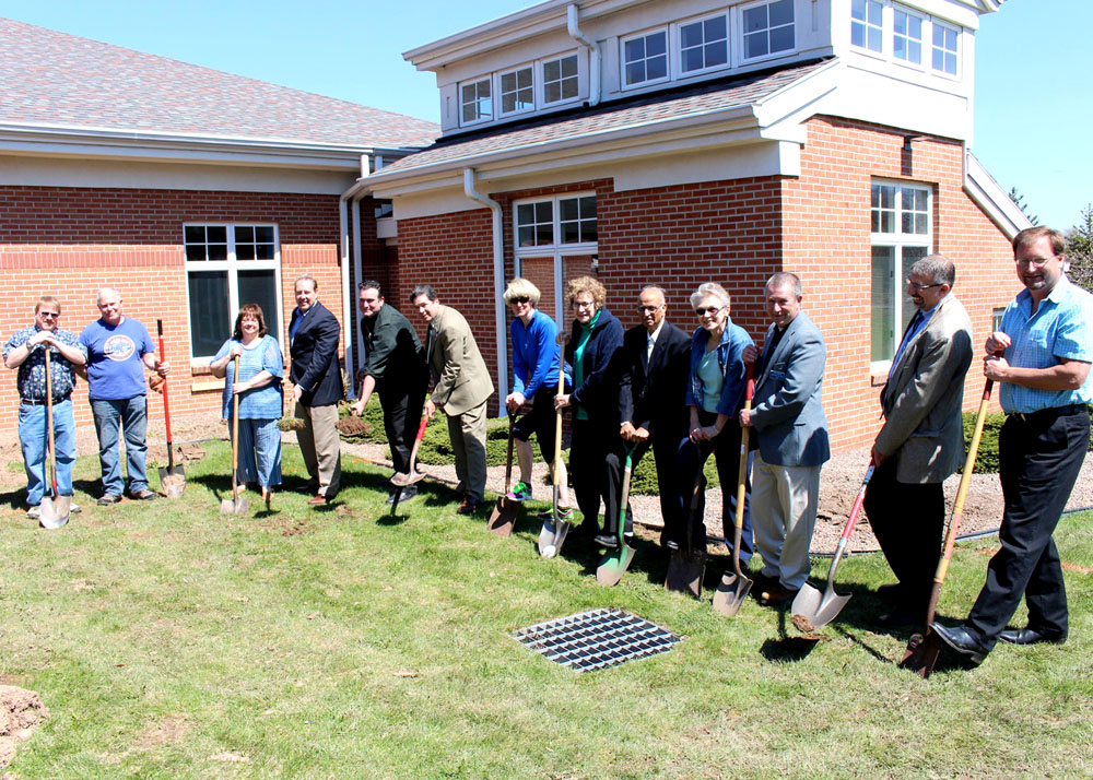 Seymour Library staff and volunteers, and local dignitaries break ground on the Local History Room addition. Shown are: (l-r) Dr. Scott Rochette, Seymour Library Board trustee; Dave Virgilio, After Hours Fundraiser Committee member; Patty Uttaro, Monroe County Library System director; Senator Joseph Robach, New York State Senate; Carl Gouveia, Seymour Library director; Supervisor Robert Carges, Town of Sweden; Mayor Margaret Blackman, Village of Brockport; Rosie Rich, Seymour Library volunteer/archivist; Dr. Sriram Bakshi, Seymour Library trustee; Debbie Cody, After Hours Fundraiser Committee chair; Barry Flansburg, community liaison for Assemblyman Steve Hawley; Tom Simbari, Simbari Design Architecture; and Rob Spaiches, Whitney East Inc. project manager. Photo by G. Griffee