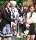 Chaplain of the Navy Club Ron Ayrault assists Oliver Middle School students Talia Danno and Giuliana Lincoln place the commemorative wreath at the base of the school's flagpole.