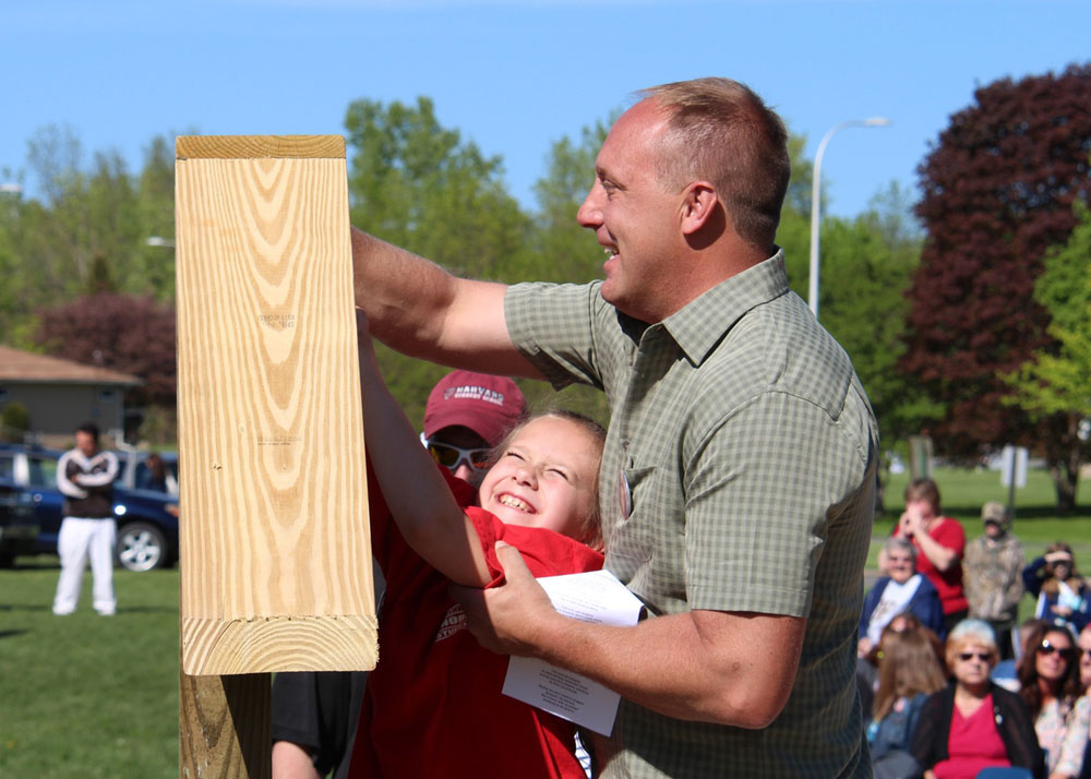 John Romansky, Jr. help his niece, Hailey, place a yellow marble in the sign that marks the dedication of the Northwood Elementary School playground to the late Pat Romansky, their mother/grandmother.