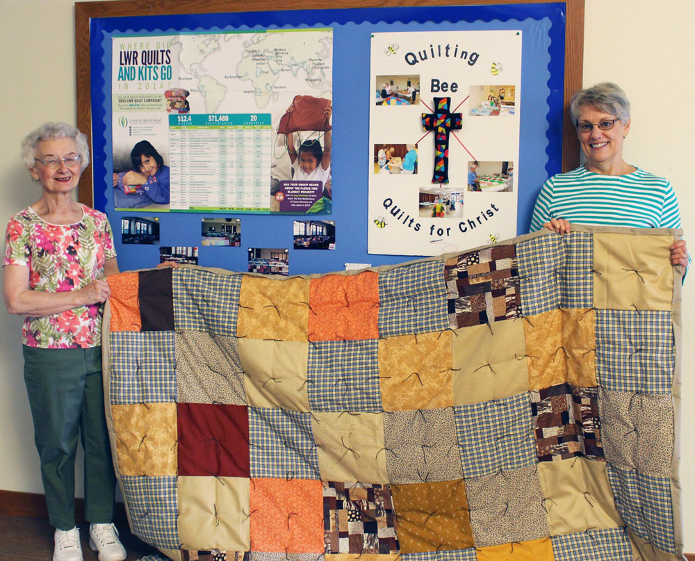 """Carolyn Hurlbutt (left) and Lois Kane hold one of the quilts the Quilts for Christ volunteer group creates for those in need around the globe. """"It's a great crew and we work really well together,"""" said Kane. G. Griffee photo"""