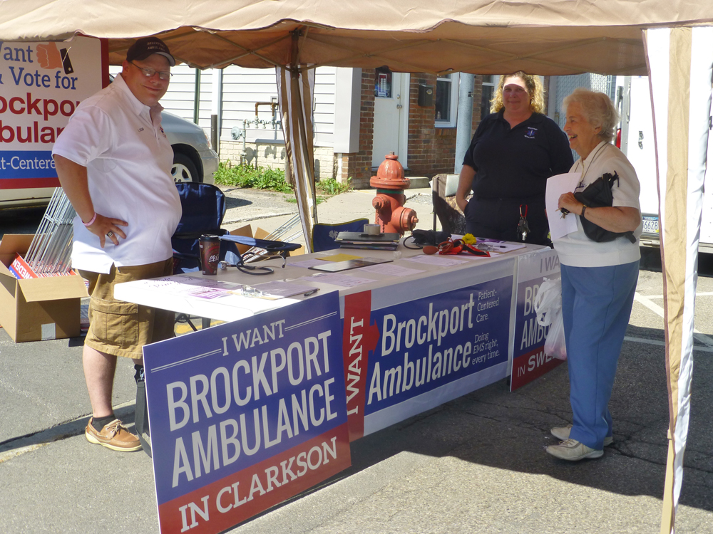 Former Sweden Supervisor Jean Brooks speaks with Brockport Ambulance Chief Cody Dean at the Brockport Farmers Market on Sunday, July 19. He and Lieutenant Sue Dann were on hand at an information booth. Signs promoting the designation of Brockport Ambulance as emergency service provider can be seen throughout the area. C. Martin photo