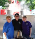 Charlie Hungerford with wife, Carolyn Hungerford (left), and daughter, Michelle Johnson (right) at the Hilton Firemen's Carnival in the Walker Fire Department Clam Booth. The fire department presented Charlie with a bell as a gift for his 50 years of service.