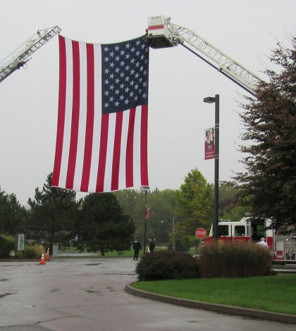 A huge U.S. flag hung from ladder trucks on the Roberts Wesleyan College campus Tuesday, September 29 for the funeral of Bergen EMT Barry Miller at Pearce Memorial Church. K. Gabalski photo