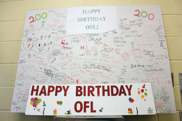 A large scale birthday card signed with greetings from library patrons congratulates Ogden Farmers' LIbrary for its 200 years of library service to the community.