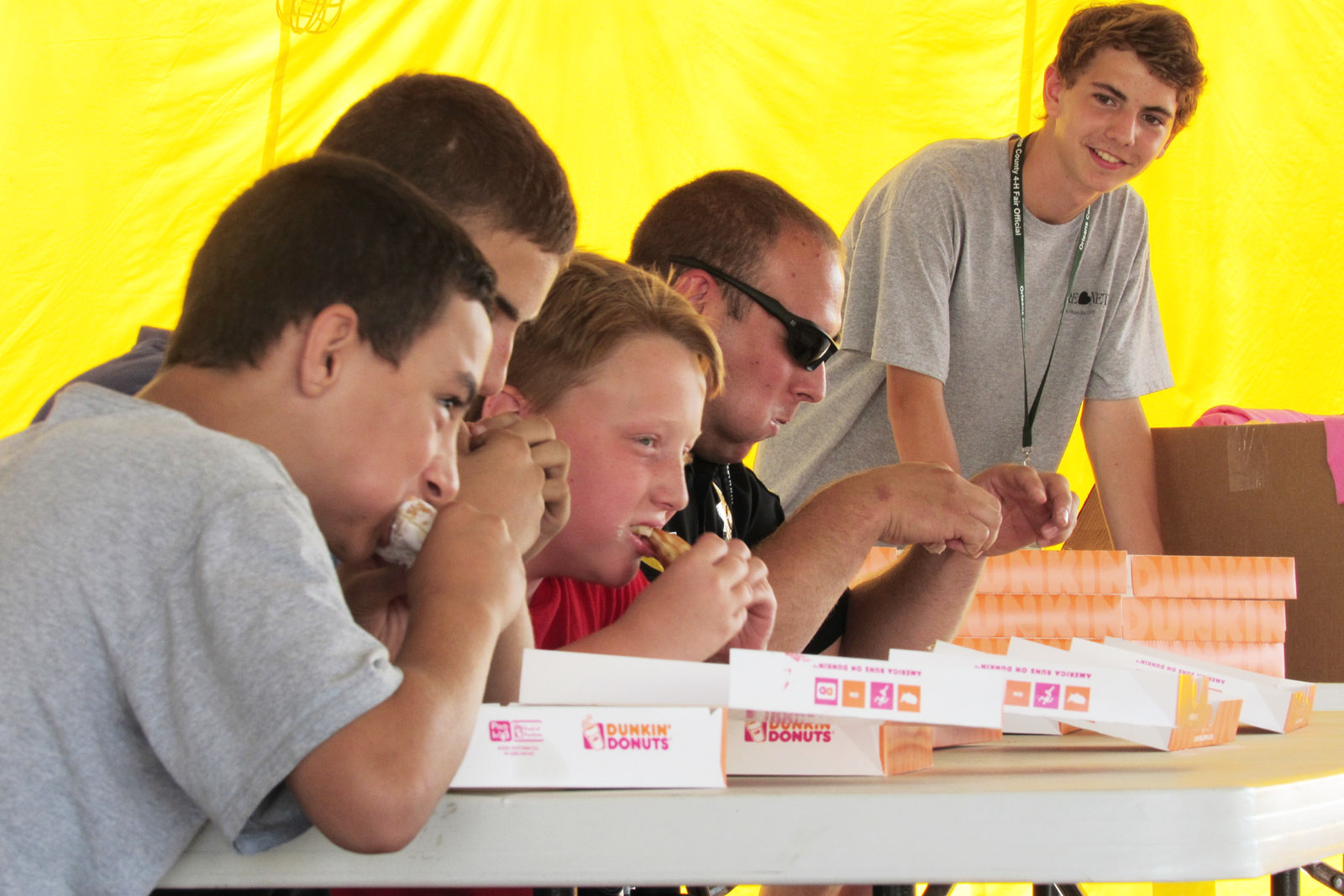 """The first-ever donut eating contest was held at this year's Orleans County 4-H Fair, July 27-Aug. 1.  Two members of the Orleans County Sheriff's Department took on donut eating """"amateurs"""" in two rounds to see who could eat the most of six donuts. Here, Orleans County Deputy Sheriff Jeff Cole (in sunglasses), competes in the first round. He lost out to the other contestants who received t-shirts for their efforts.  Deputy Cole joked that he lost because he prefers eating bagels. Looking on is Zachary Moore, the 2014 Orleans County 4-H Fair Duke. Orleans County Sheriff's Department investigator Ken Strickland participated in the second round and also lost out to the """"amateur"""" contestants. Donuts were donated by Dunkin Donuts. K. Gabalski photo"""