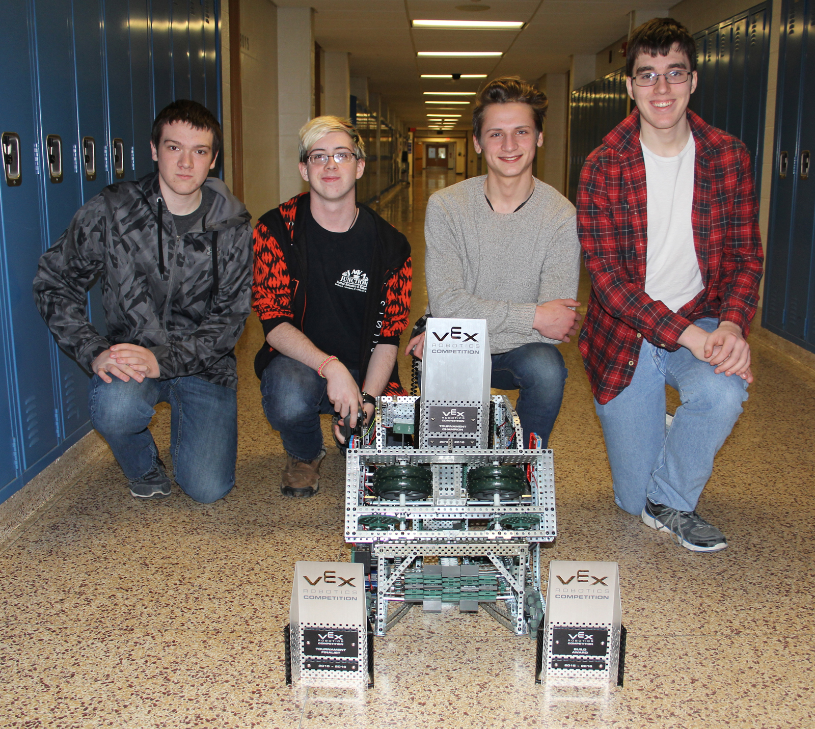 Eric Toepper, Connor Noble, William Levchuk and Dan Fletcher show off their robot and trophies. Provided photo