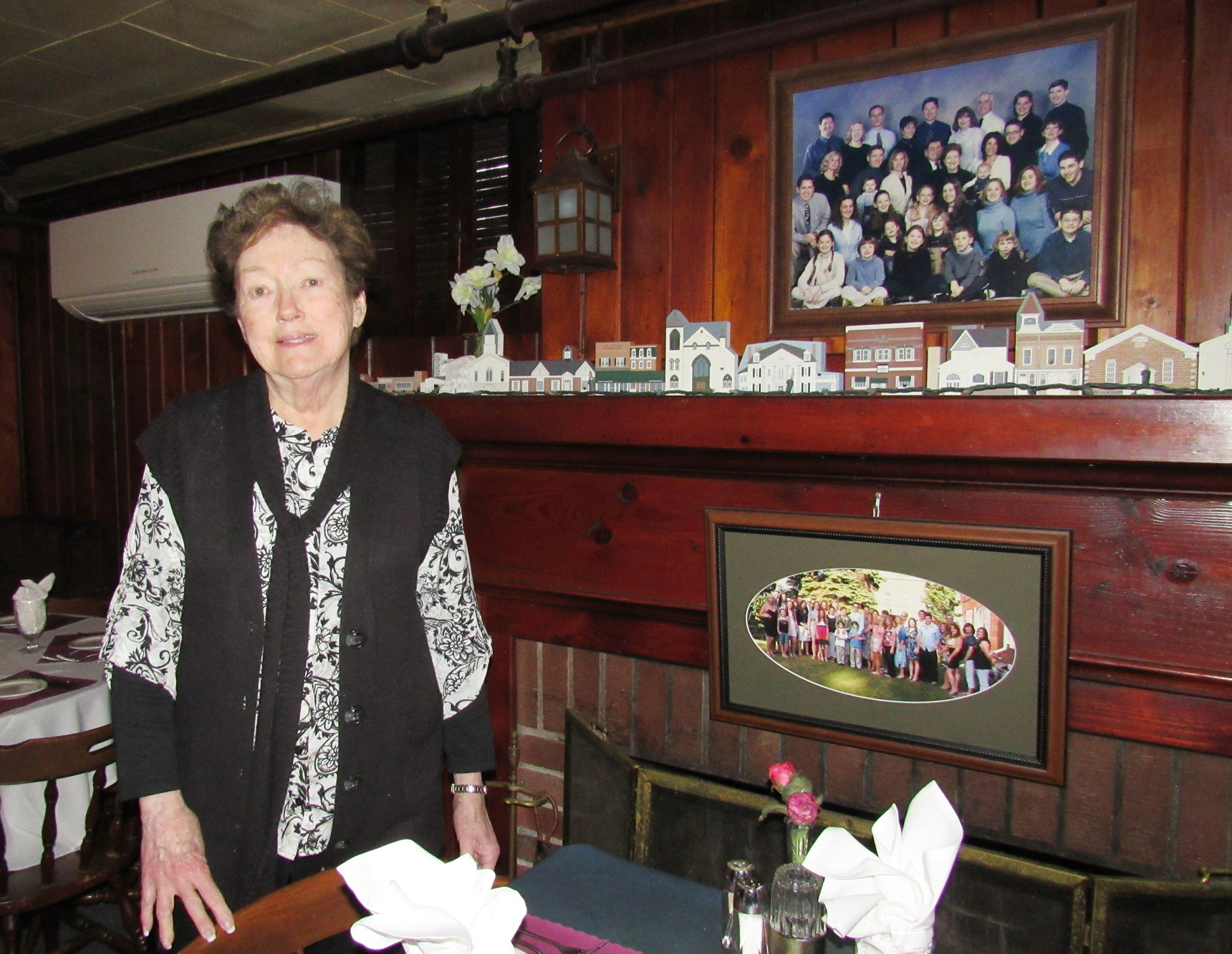 Peggy Naughton poses in the dining area of the Johnson House Restaurant. The photos over and on the fireplace mantel are her children and grandchildren. K. Gabalski photo