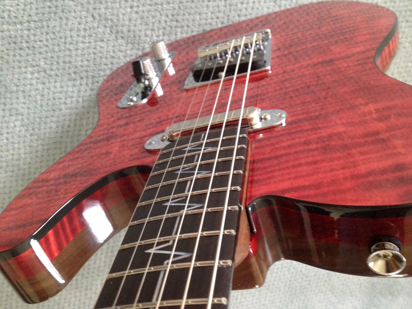 A close-up of the top and neck of the guitar consisting of multi-piece black walnut construction. Provided photo